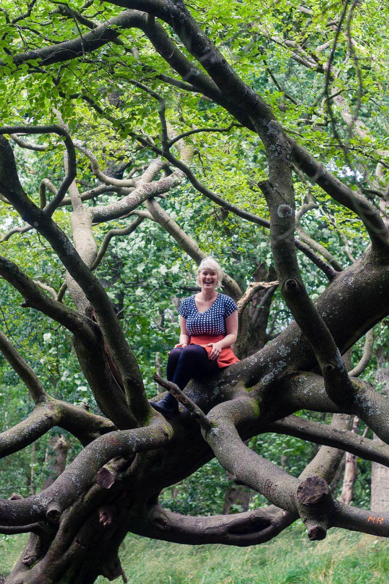 A woman climbing trees at Seven Lochs Wetland Park, Glasgow, Scotland