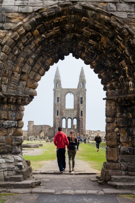 A couple walking through the archway of the ruined St Andrews Cathedral.