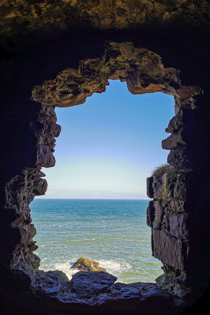 Sea view through a stone window at Dunnottar Castle in Scotland