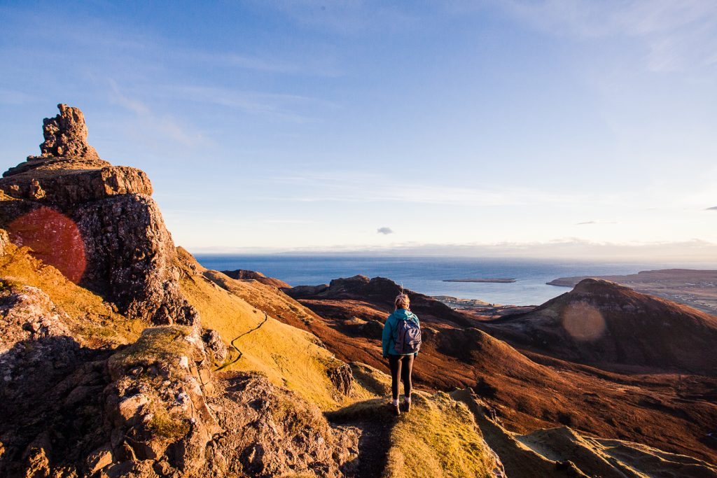 A woman standing next to rock formations in the Scottish Highlands looking down towards the sea.