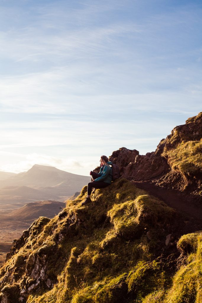 A woman sitting on a steep, rocky hillside in Scotland with blue sky in the background