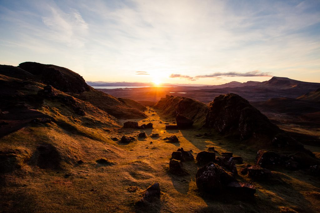 The sun rising over the horizon above the hills on the Isle of Skye