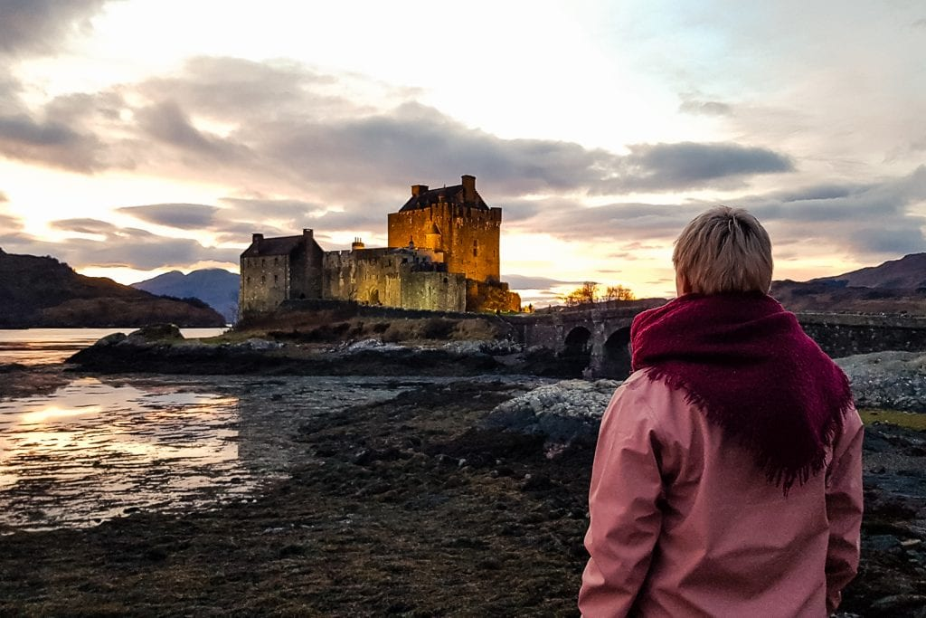 Women watching the sunset at Eilean Donan Castle in Scotland.