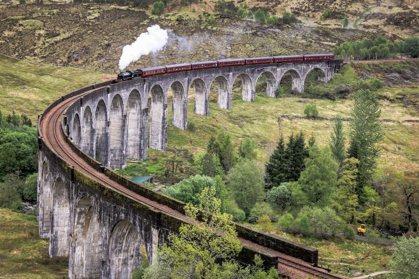 The Jacobite Steam Train crossing the Glenfinnan Viaduct in the Scottish Highlands.
