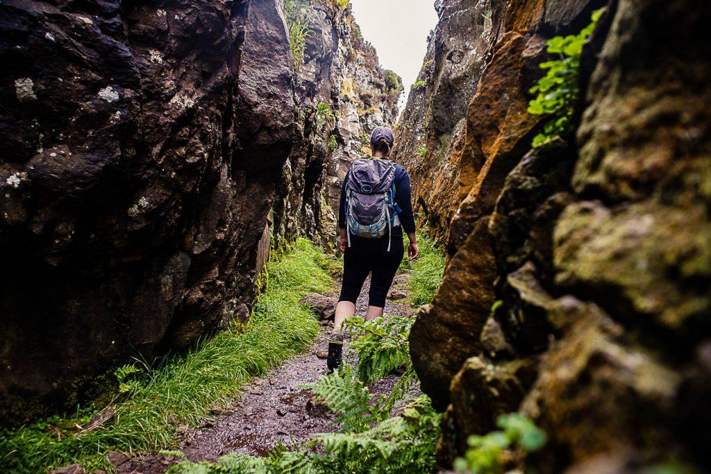 A woman hiking through the gorge at The Whangie walk near Glasgow