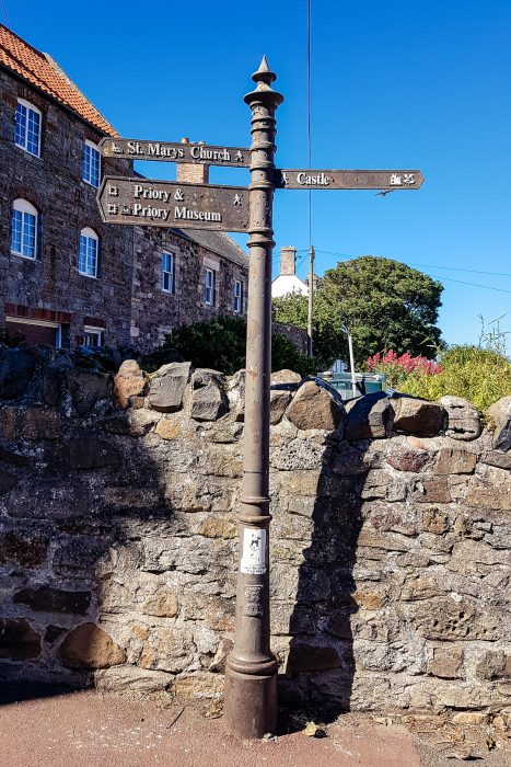 A waymarker pointing towards the many things to do in Lindisfarne on the Holy Island.