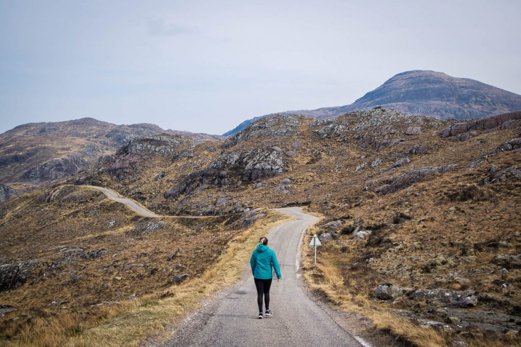 A woman walking on a single-track road in Scotland