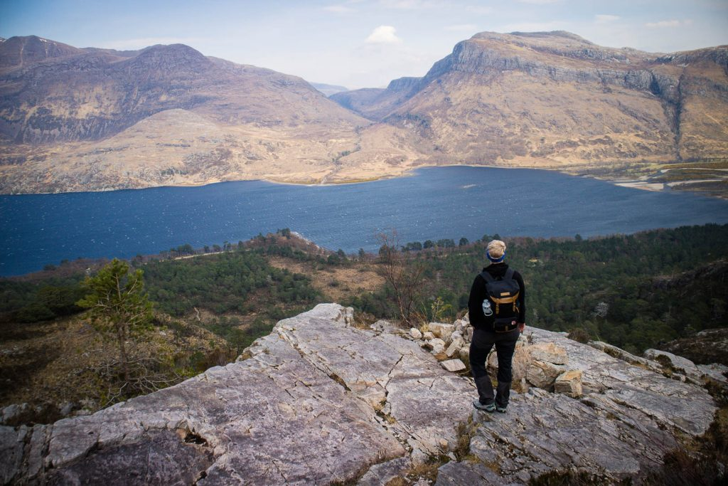 A woman standing on a rocky plateau surrounded by mountains and a lake in Scotland