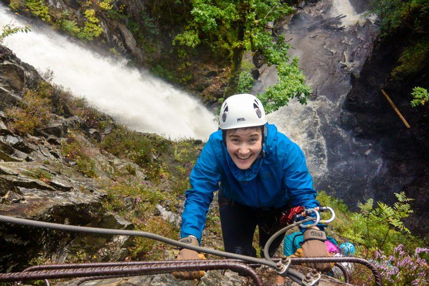A woman climbing the Via Ferrata in Scotland