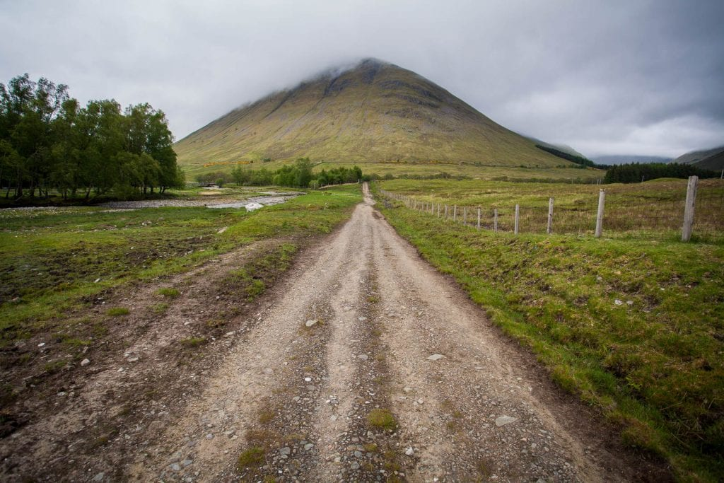 A trail leading towards a cloud-covered mountain in Scotland.
