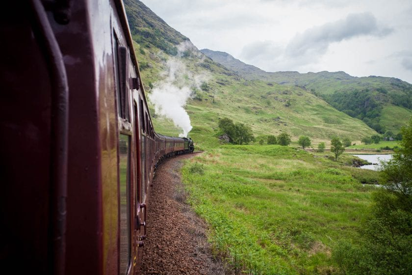 Looking of the Jacobite Steam Train as is makes its way through the lush green hills of the Scottish Highlands.
