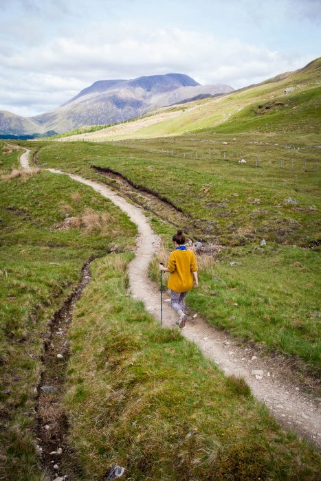 A woman walking on a foot path towards Ben Nevis.