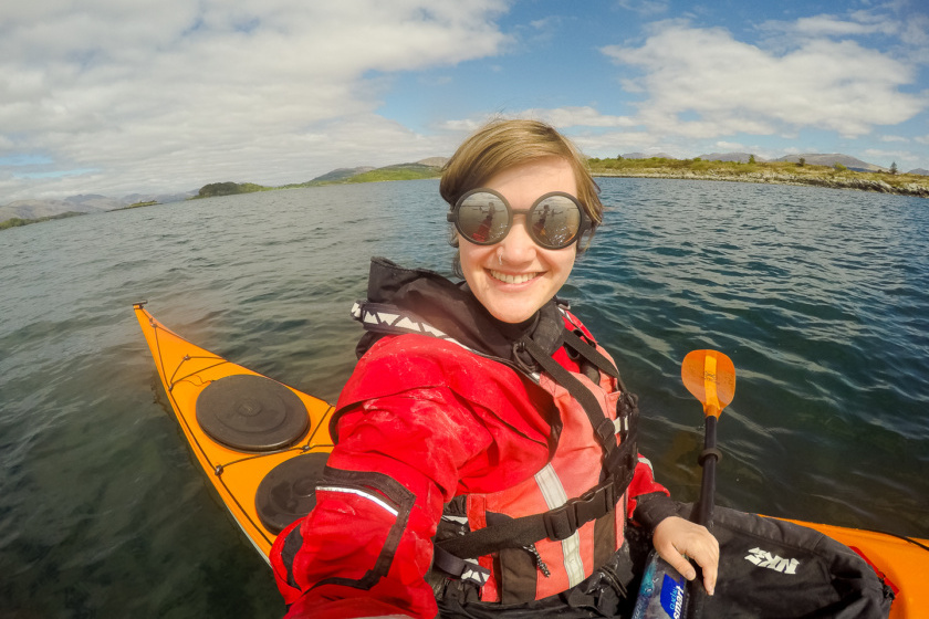 a woman in a sea kayak in scotland